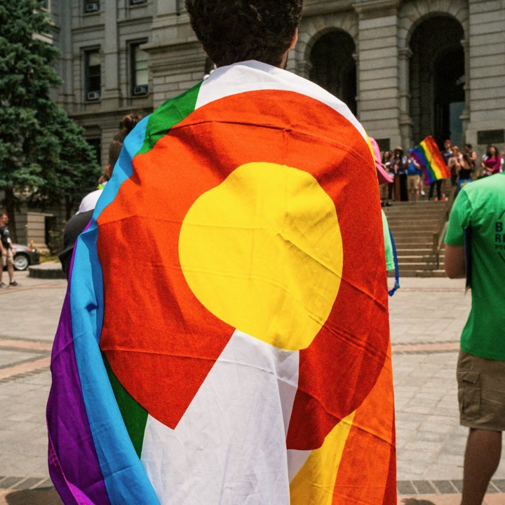 Person carrying the Colorado flag with the LGBTQ colors to represent his support to the LGBTQ community